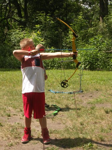 Boy taking aim with bow & arrow at archery range