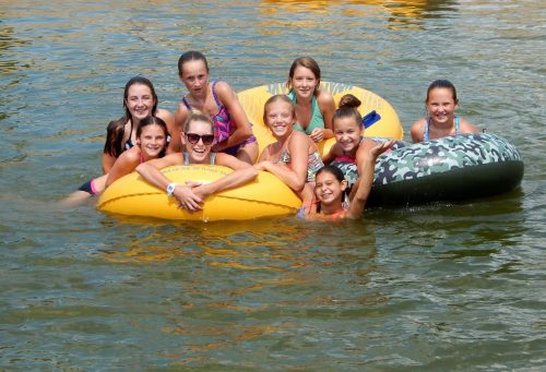 Cabin of girls smiling on inner tubes in lake