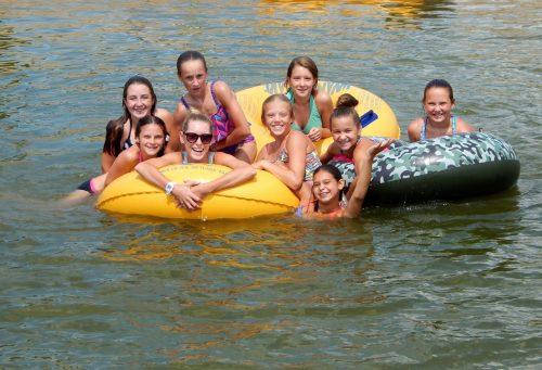 Cabin of girls smiling on inner tubes in lake