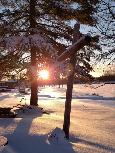 Sunrise behind cross at snow covered Ebenezer