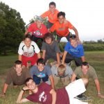 Ten boys in pyramid with counselor