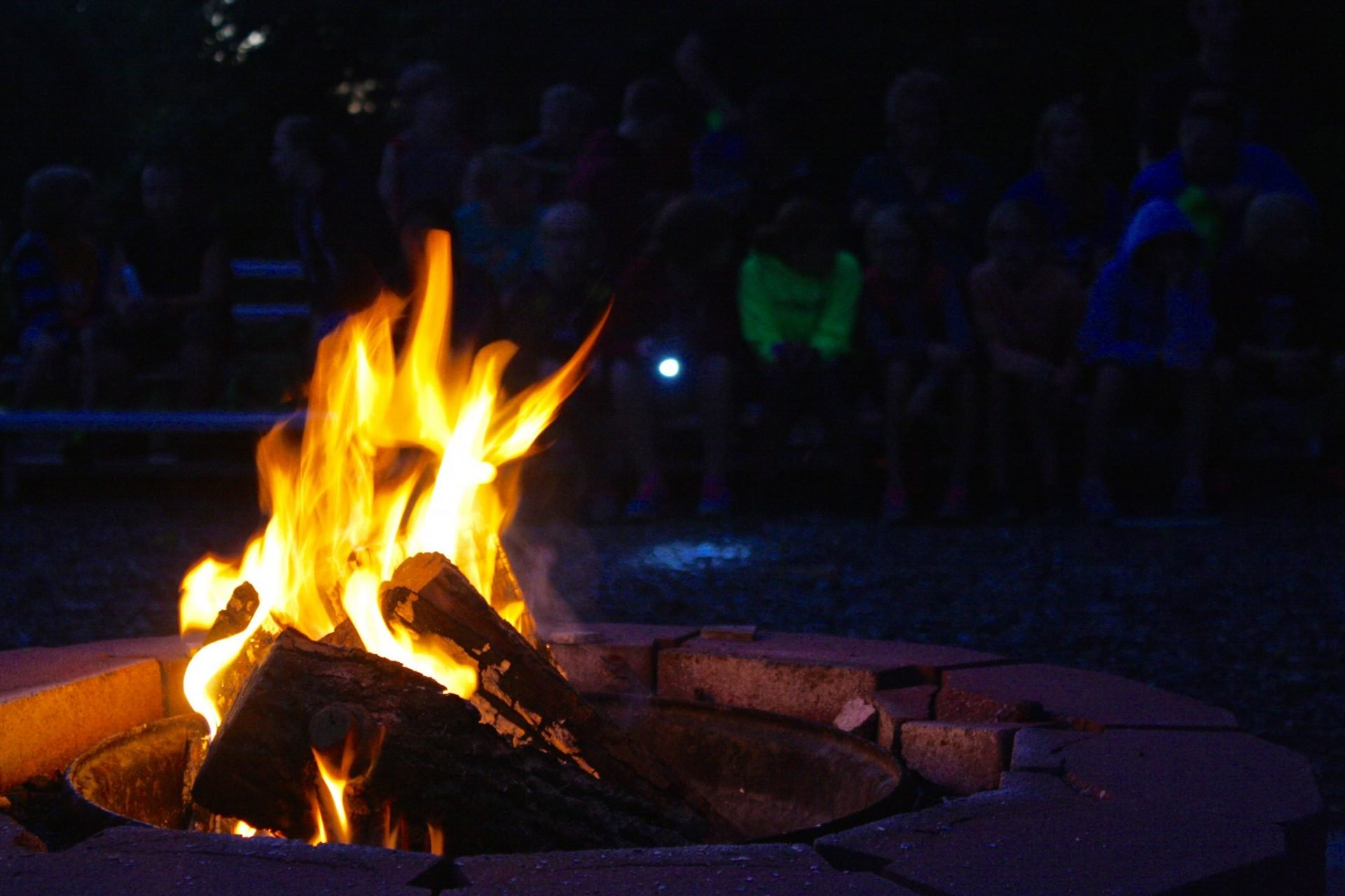 Ebenezer campfire at night with group on benches