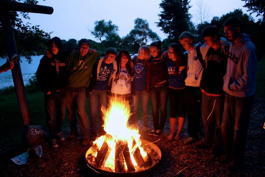 Group of youth standing around Ebenezer fire