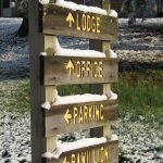 Signpost directing toward lodge, office, parking, and pavilion.