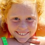 Red-headed girl smiling on the beach