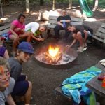 Younger group around fire at treetop villages.