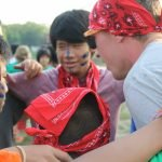 Counselor scheming with campers during an all camp game.
